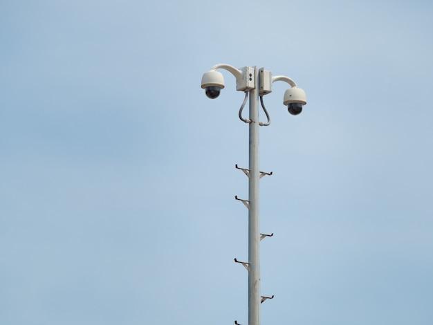 Купольная система видеонаблюдения на 360 градусов установлена на колонне против голубого неба. Premium Фотографии