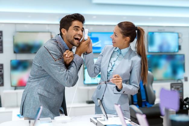 Пара, одетая в деловую одежду, пробует камеру на 360 градусов, стоя в техническом магазине Premium Фотографии