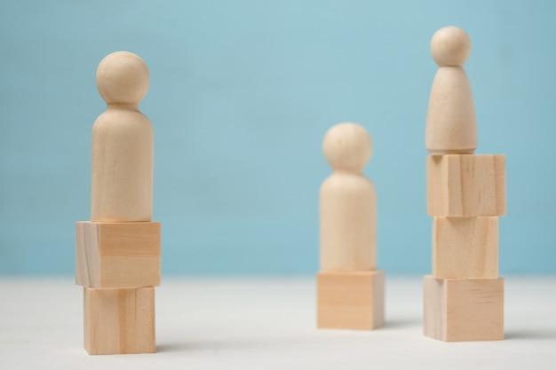 人々の3つの抽象的な木製図は異なるレベルに立っています。 Premium写真