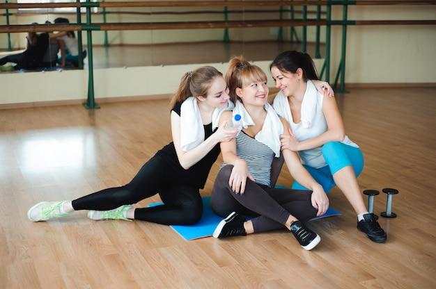 3人の陽気なスポーツウーマンがジムでエクササイズした後、笑って楽しんでいます。かわいい女性はハードな身体活動の後に休憩を取る Premium写真