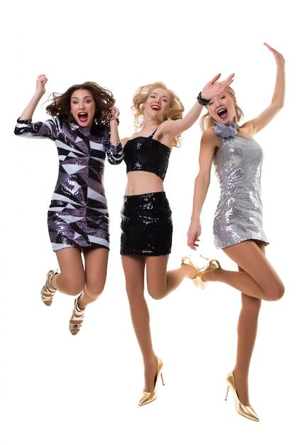 光沢のあるドレス - 分離の白のスタジオで踊る3人のかわいいヨーロッパの女の子 Premium写真