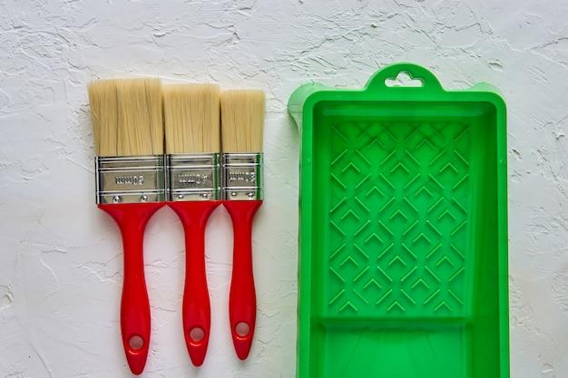 赤いハンドルと白いコンクリートの緑のペイントトレイを持つ3つのブラシ。家の改修のためのツールとアクセサリー。上面図 Premium写真