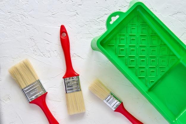 赤いハンドルと白いコンクリートの背景に緑色の塗料トレイを持つ3つのブラシ。家の改修のためのツールとアクセサリー。上面図 Premium写真