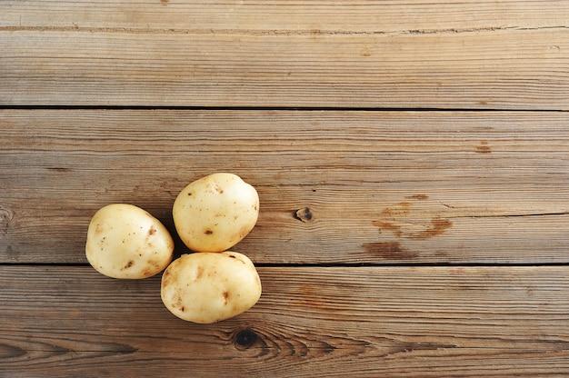 素朴な木製の表面に3つの若い塊茎生白いジャガイモ Premium写真