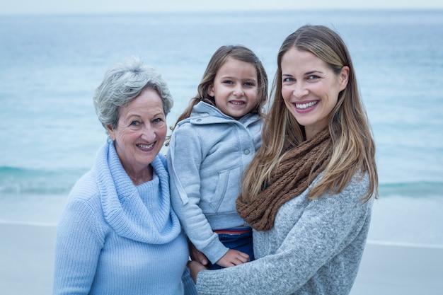 ビーチに立っている女性の幸せな3世代 Premium写真