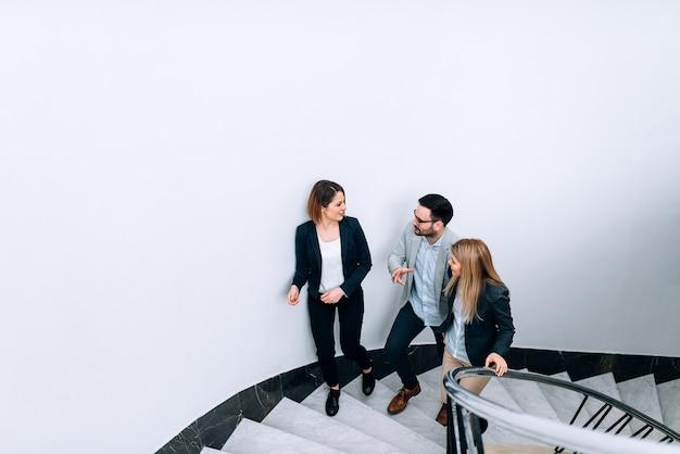 事務所ビルの階段を上りながら話している3人の人々。 Premium写真