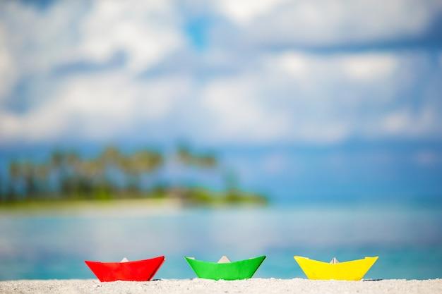 ターコイズブルーの海に3つのカラフルなペーパーボート。 Premium写真