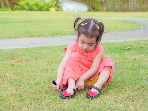 彼女の靴を履こうとしているオレンジ色のドレスと3歳のかわいい女の子。 Premium写真