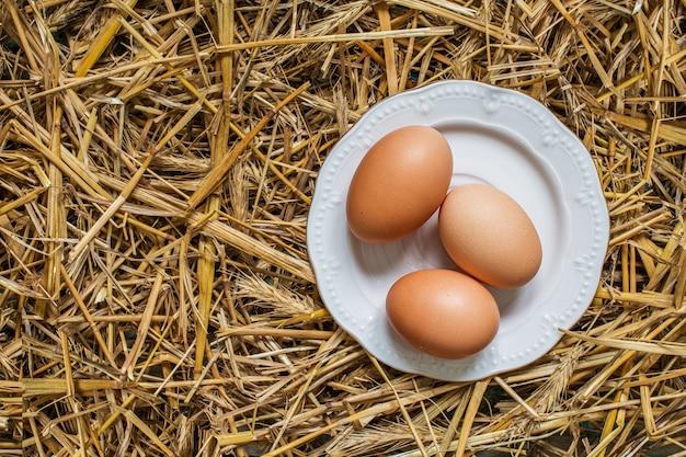 わらのプレートに3つの卵 Premium写真