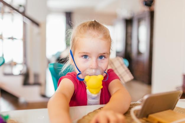 アレルギー性喘息の3歳の子供。疲れた目で見ながら、子供のスペーサーから薬を吸入します。 Premium写真