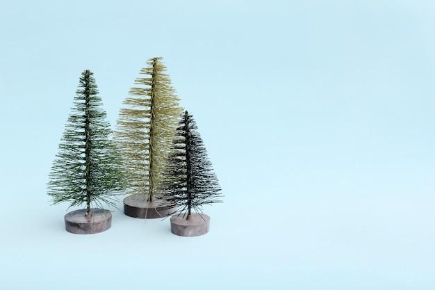 最小限のスタイルで明るい背景に3つのクリスマスツリー。 Premium写真