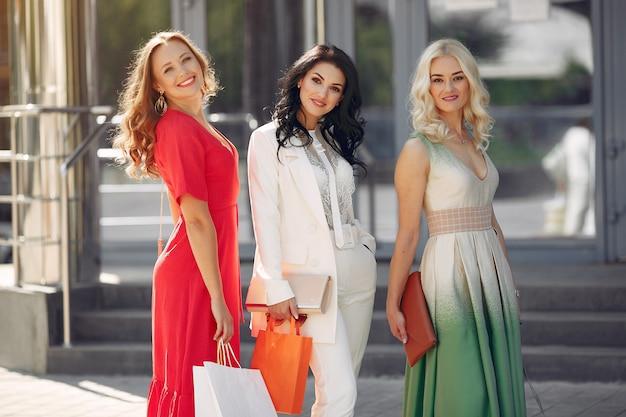 街で買い物袋を持つ3つのエレガントな女性 無料写真