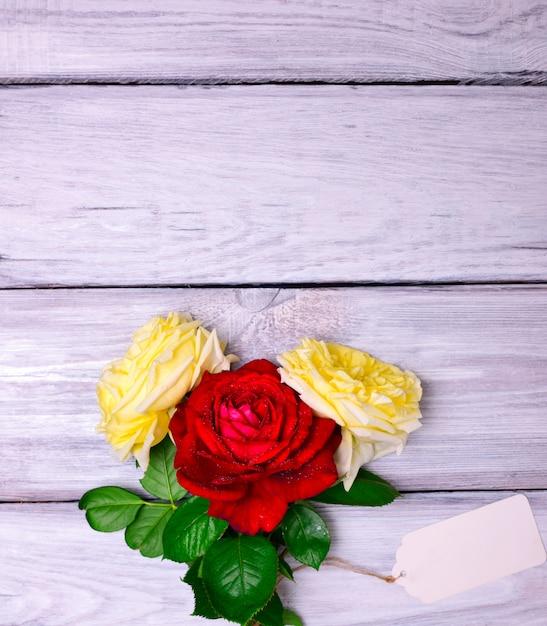 3つの開花バラとホワイトペーパータグ Premium写真