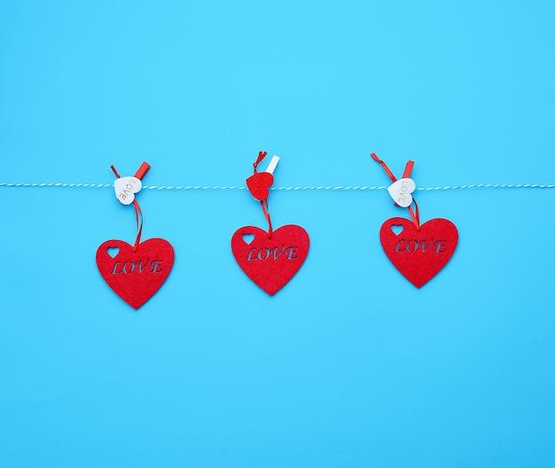 3つの赤いフェルトハートが白いロープにぶら下がっていて、洗濯はさみで固定 Premium写真
