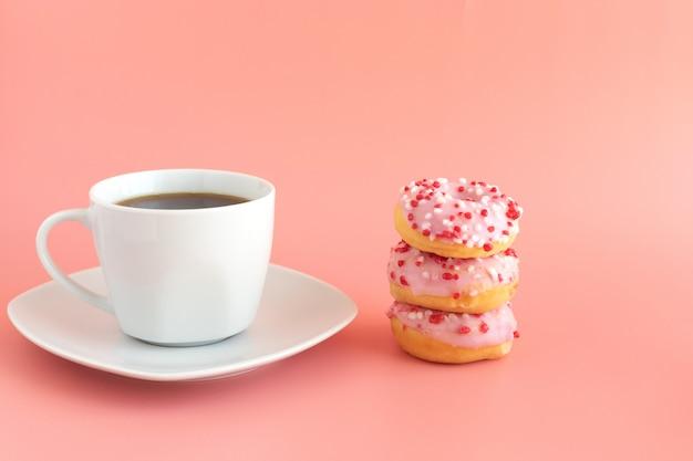 新鮮なブラックコーヒー、エスプレッソ、3つのドーナツ、ピンクのアイシング、ピンクの次のホワイトコーヒーカップ Premium写真