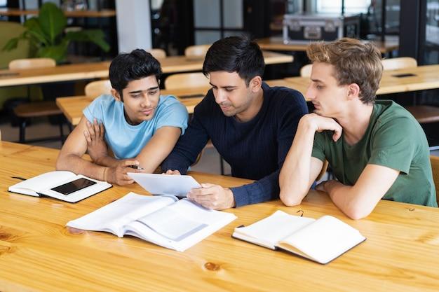 タブレットコンピュータを勉強して使用する3人の真剣な学生 無料写真