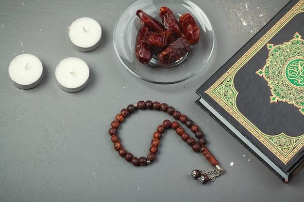 日付のフルーツ、コーラン、木製のロザリオビーズイスラム教徒のラマダン、祝福された金曜日のメッセージと3か月の概念 Premium写真