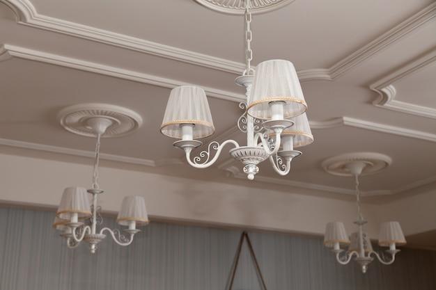 3つの電気ランプとランプシェードが天井に掛かっているシャンデリア Premium写真