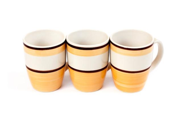 白い表面に分離された3つのマグカップの行 Premium写真