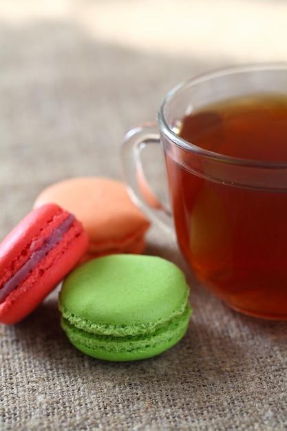赤、緑、オレンジのマカロン3個と黄麻布のテーブルクロスにお茶とマグカップ。垂直フレーム。 Premium写真