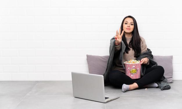 ポップコーンのボールを保持し、幸せと指で3つを数えるラップトップで映画を見せてコロンビア少女 Premium写真