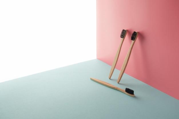 3つの竹、木製の歯ブラシは、白、青、ピンクの背景にあります。コピースペースの概念、幾何学的構成。医学概念、ブラッシング、環境に優しい、処理、堆肥 Premium写真