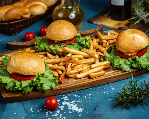 3つの小さなビーフハンバーガーとフライドポテトを木の板で提供 無料写真