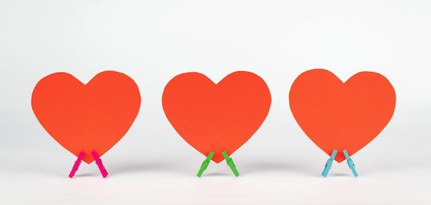 3つの紙の心のセットは、白い背景の上の木製の洗濯はさみの上に立ちます。最小限の愛の概念。 Premium写真