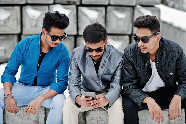 サングラスの3つのカジュアルな若いインド人のグループは、石のブロックに対して提起され、携帯電話を見ています。 Premium写真