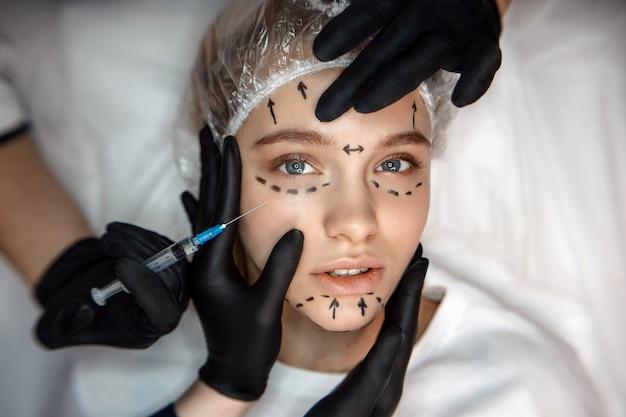ソファに横たわって集中してリラックスした若い女性とまっすぐに見えます。彼女の顔はマークされています。片手で注射用シリンジを保持します。別の3つのタッチ顔。 Premium写真