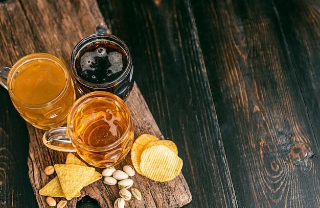高価なクラフトビールを3杯。クラシックで濾過されておらず、テーブルのグラスに暗い色のピーナッツとピスタチオチップとナチョスのスナック Premium写真
