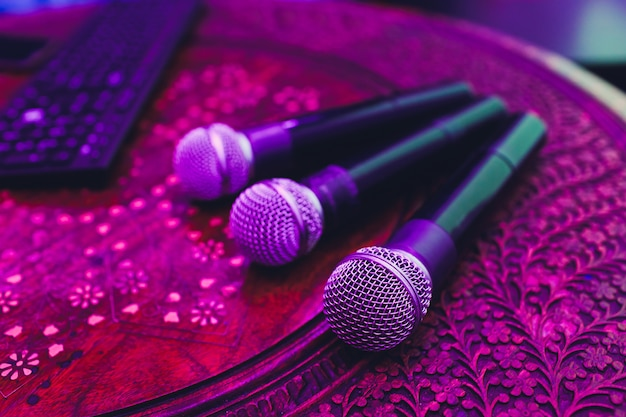 3 микрофона в группе на красной таблице с космосом экземпляра. Premium Фотографии