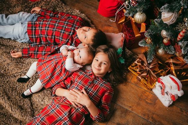 3人の子供がクリスマスツリーの横にあります。 Premium写真