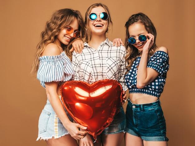 格子縞のシャツの夏服で3人の笑顔の美しい女性。ポーズの女の子。サングラスにハート形のバルーンが付いたモデル。バレンタインデーのお祝いの準備ができて 無料写真