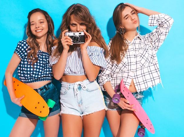 カラフルなペニースケートボードを持つ3つの美しいスタイリッシュな笑顔の女の子。夏の女性。レトロな写真カメラで写真を撮る 無料写真