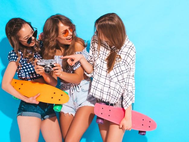 カラフルなペニースケートボードと3つのセクシーな美しいスタイリッシュな笑顔の女の子。夏の女性は格子縞のシャツ服ポーズします。レトロな写真カメラで写真を撮るモデル 無料写真
