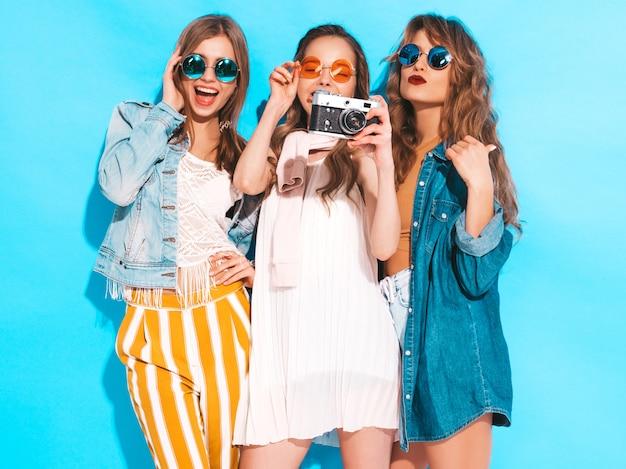 トレンディな夏のカラフルなドレスとサングラスの3人の若い美しい笑顔の女の子。セクシーな屈託のない女性がポーズします。レトロなカメラで写真を撮る 無料写真