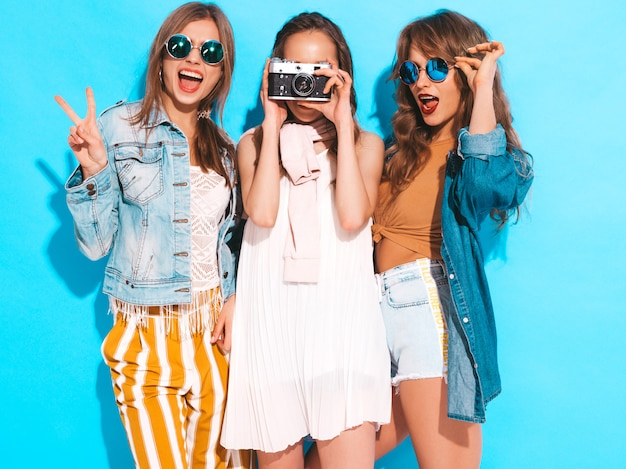トレンディな夏のカジュアルドレスとサングラスの3人の若い美しい笑顔の女の子。セクシーな屈託のない女性がポーズします。レトロなカメラで写真を撮る 無料写真