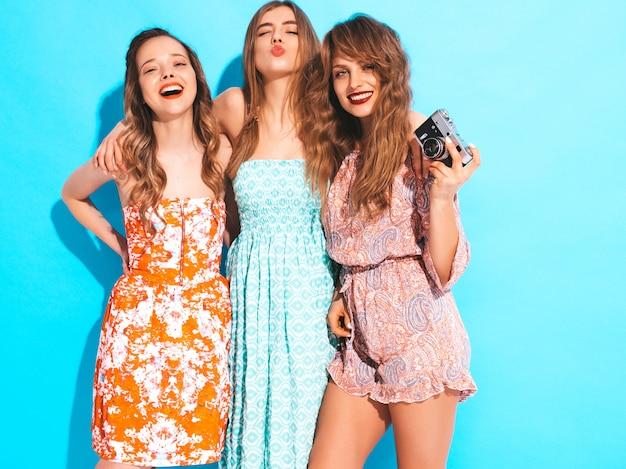 トレンディな夏のカラフルなドレスの3人の若い美しい笑顔の女の子。セクシーな屈託のない女性がポーズします。レトロなカメラで写真を撮る 無料写真