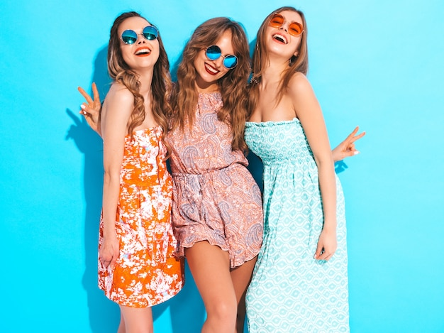 トレンディな夏のカラフルなドレスの3人の若い美しい笑顔の女の子。サングラスでセクシーな屈託のない女性。 無料写真