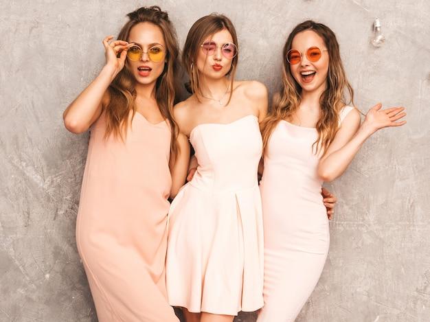 トレンディな夏の3人の若い美しい笑顔の女の子はピンクのドレスを光します。セクシーな屈託のない女性がポーズします。楽しいラウンドサングラスの肯定的なモデル 無料写真