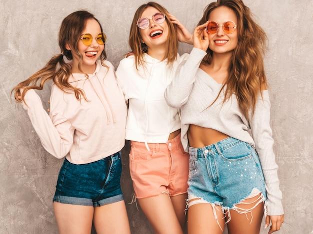 トレンディな夏の3人の若い美しい笑顔の女の子は服をスポーツします。セクシーな屈託のない女性がポーズします。楽しいラウンドサングラスの肯定的なモデル。ハグ 無料写真