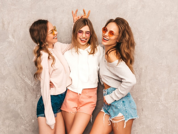 トレンディな夏の3人の若い美しい笑顔の女の子は服をスポーツします。セクシーな屈託のない女性がポーズします。楽しんでいる丸いサングラスのモデル。指で頭に角を作ります 無料写真