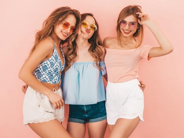 トレンディな夏服で3人の若い美しい笑顔の女の子。セクシーな屈託のない女性がポーズします。楽しいポジティブモデル。ハグ 無料写真