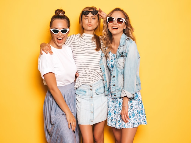 トレンディな夏服で3人の若い美しい笑顔流行に敏感な女の子。黄色の壁に近いポーズセクシーな屈託のない女性。サングラスを楽しんでいるポジティブなモデル 無料写真