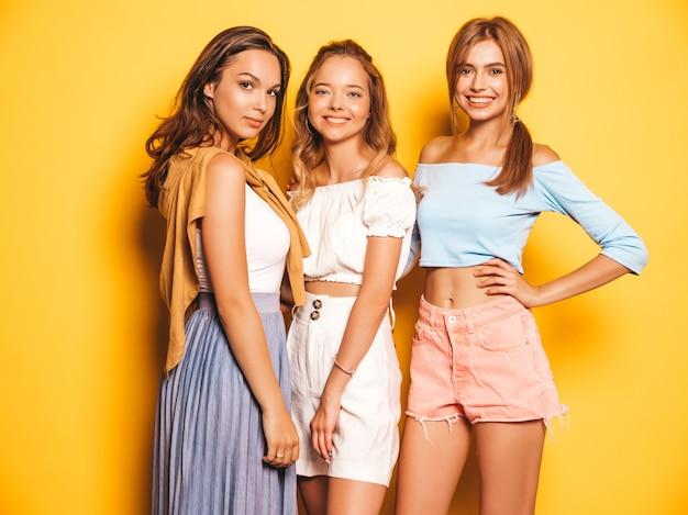 トレンディな夏服で3人の若い美しい笑顔流行に敏感な女の子。黄色の壁に近いポーズセクシーな屈託のない女性。楽しいポジティブモデル 無料写真