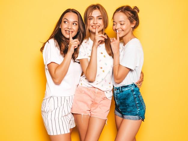 トレンディな夏服で3人の若い美しい笑顔流行に敏感な女の子。黄色の壁の近くでポーズセクシーな屈託のない女性。 無料写真