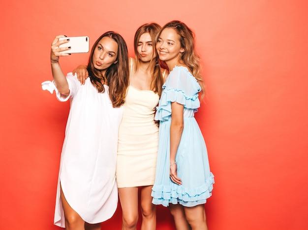 トレンディな夏服で3人の若い美しい笑顔流行に敏感な女の子。ピンクの壁に近いポーズセクシーな屈託のない女性。ポジティブなモデルが夢中になります。スマートフォンでセルフポートレート写真を撮る 無料写真