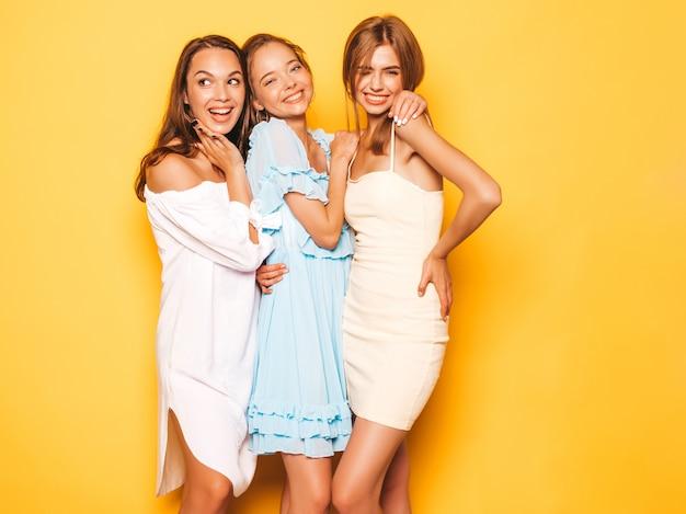 トレンディな夏服で3人の若い美しい笑顔流行に敏感な女の子。黄色の壁に近いポーズセクシーな屈託のない女性。ポジティブなモデルが夢中になって楽しんでいる 無料写真
