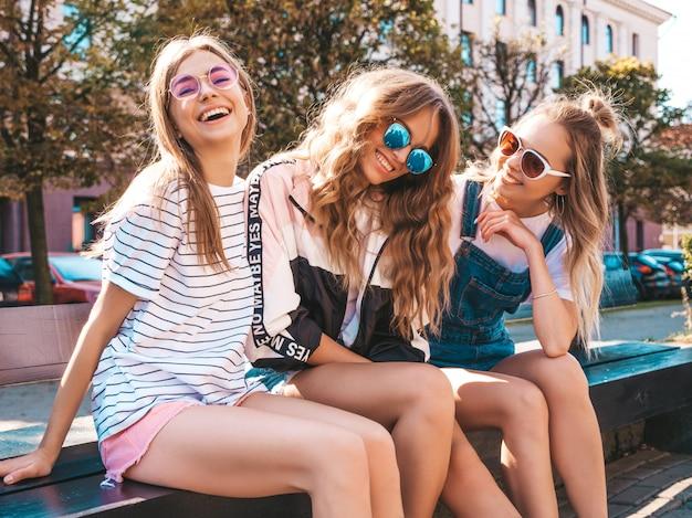 トレンディな夏服の3人の若い美しい笑顔流行に敏感な女の子の肖像画。通りのベンチに座っているセクシーな屈託のない女性。サングラスで楽しんでいるポジティブなモデル 無料写真